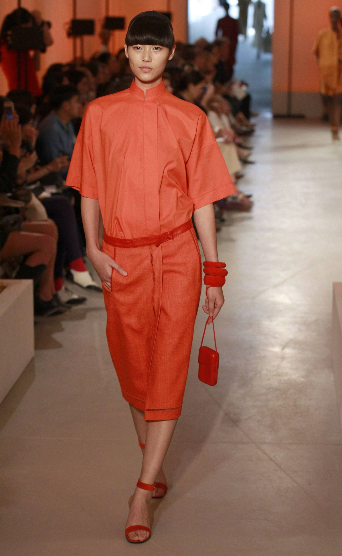 What would an Hermès ready-to-wear collection be without some of its iconic orange? Even better: orange on orange. Note the off-centre pleating, stitched H-diamond and smoothly defined lapels. Note also the purse, large enough for a mobile device and not much more.