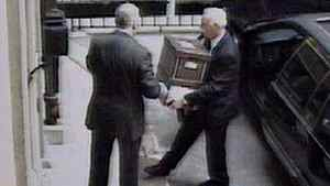Security cameras show Conrad Black, left, handing boxes to his chauffeur John Hillier outside the Hollinger Inc. office on May 20, 2005, in Toronto. Black was found guilty on the obstruction of justice charge, stemming from his removal of a dozen boxes from his Toronto offices in 2005 despite a Canadian court order sealing the premises.