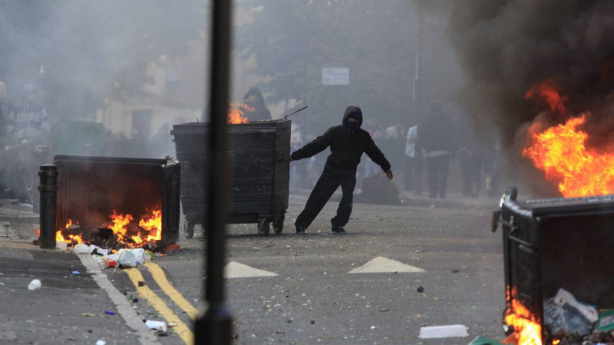 A masked youth pulls a burning garbage bin set on fire by rioters in Hackney, east London, Monday Aug. 8, 2011.