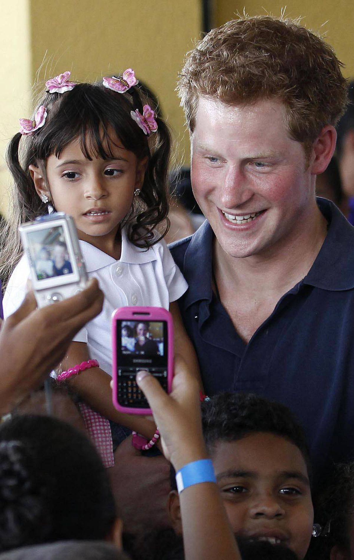CHARMING Britain's Prince Harry holds Mayara Pereira, 3, as he visits the occupied community of Complexo do Alemao in Rio De Janeiro, March 10, 2012.