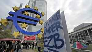 Demonstrators stand between protest banners underneath the euro sign in front of the European Central Bank in Frankfurt, central Germany, Monday, Oct. 17, 2011. Protestors gathered at many major European cities last Saturday to join in demonstrations against corporate greed and inequality and to support the US movement ' Occupy Wall Street'. About 150 protestors in Frankfurt remained at that place , some with tents.