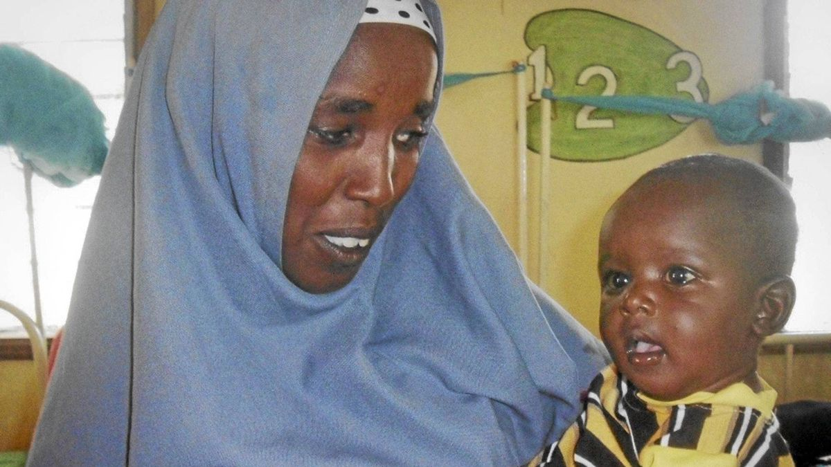 In this photo released by the International Rescue Committee, Minhaj Gedi Farah is held in the arms of his mother Asiah Dagane in the International Rescue Committee (IRC) hospital in Dadaab, Kenya Wednesday, Oct. 19, 2011.