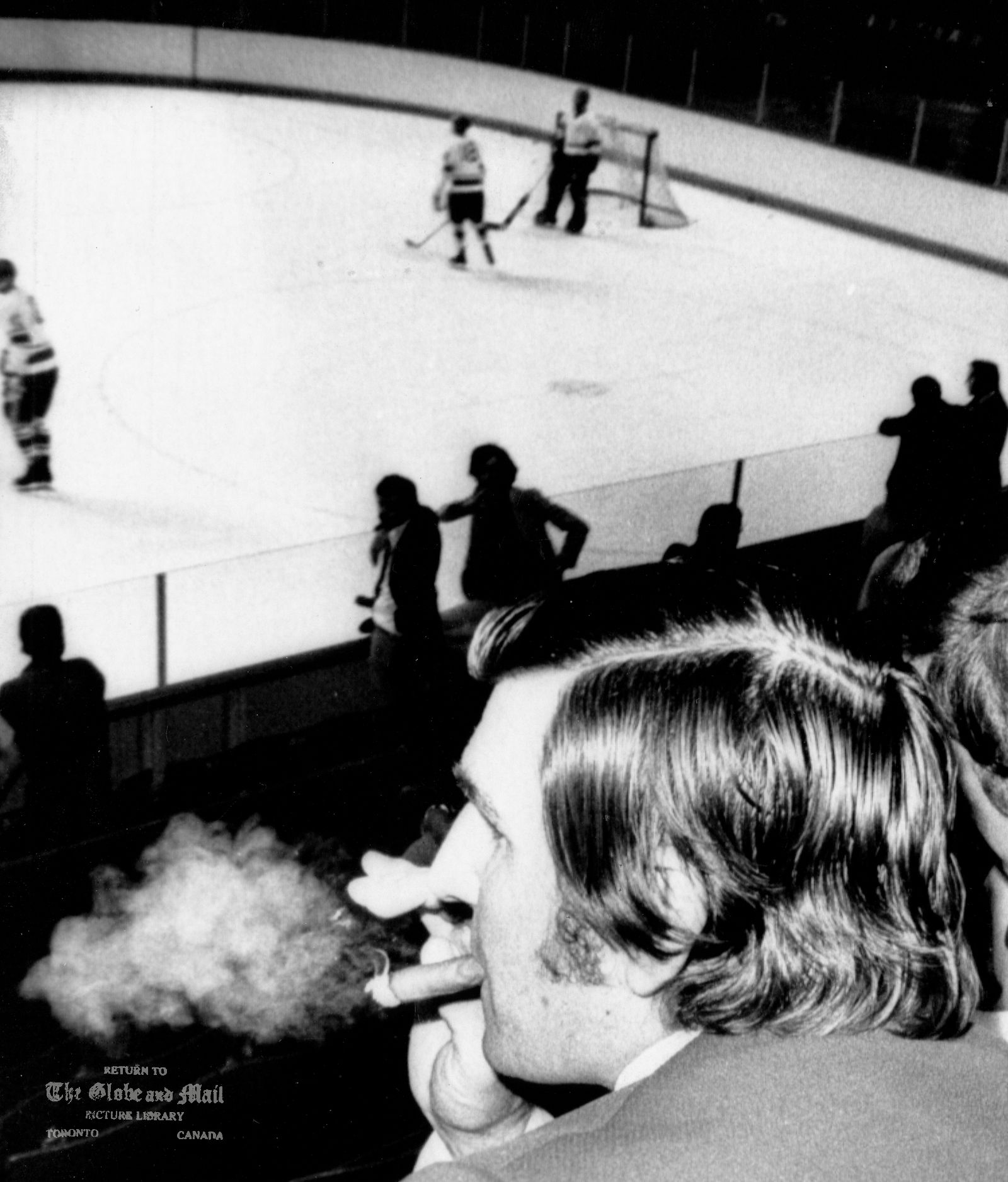 SEPTEMBER 1, 1972 -- MONTREAL -- RUSSIAN NATIONALS TRAINING -- Team Canada assistant coach, John Gerguson, puffs vigorously on a cigar while watching the rival Soviet hockey team practice at an arena in St. Laurent, a suburb of Montreal on Frdiay, Sept. 1, 1972. CP PHOTO