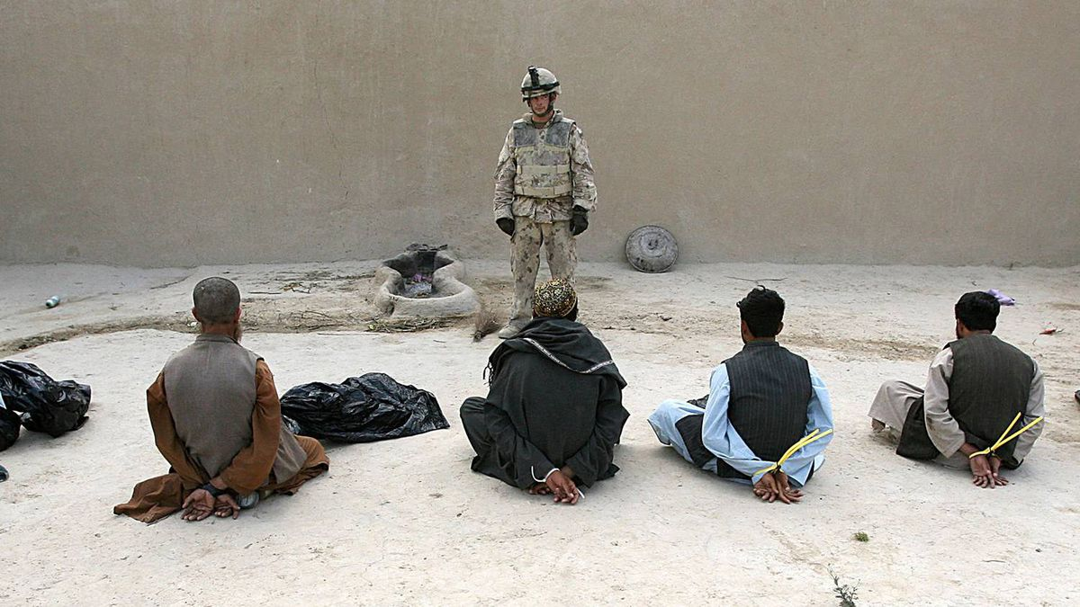 A member of Reconnaissance Platoon, 1st Princess Patricia's Canadian Light Infantry, guards six of ten suspected Taliban prisoners captured in a raid on a compound in Northern Kandahar, in this May, 2006 file photo.