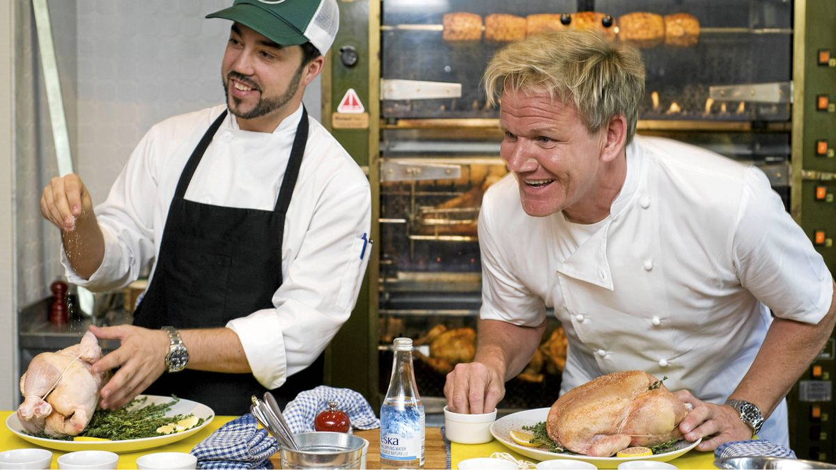 Chef Gordon Ramsay, right, speaks to reporters during a cooking demonstration at his new restaurant Laurier Gordon Ramsay, in Montreal, Tuesday, Aug. 9, 2011, as head chef Guillermo Russo looks on.
