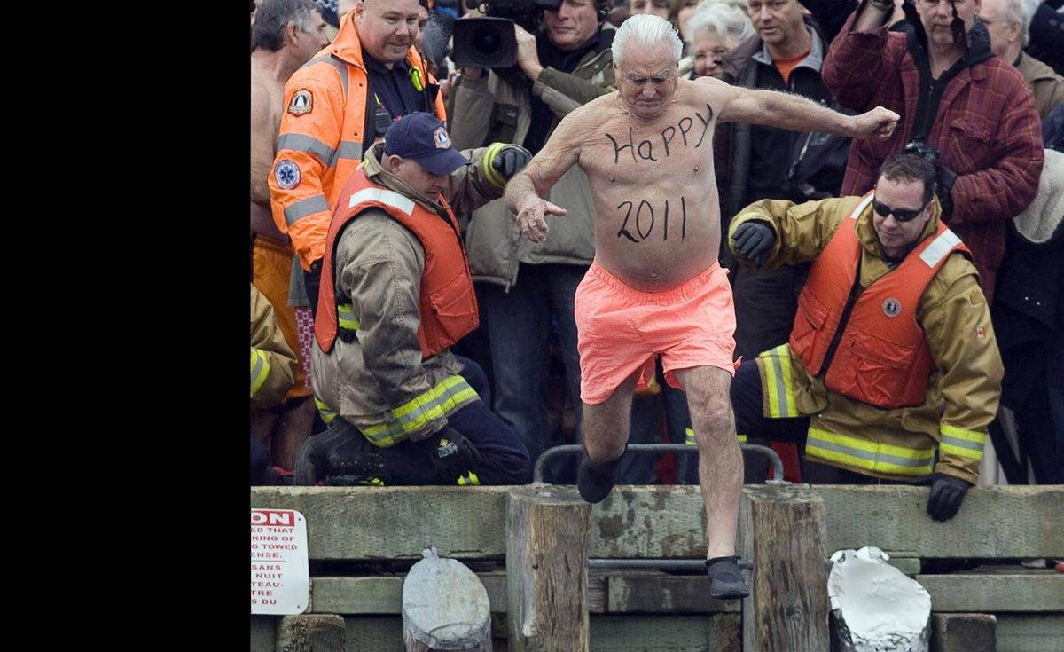 Ernie Ross, 76, jumps from the government wharf as he participates in the annual polar dip in Herring Cove, N.S. on Saturday, Jan. 1, 2011. About 100 people registered to jump into the ocean to welcome the new year and support Feed Nova Scotia.