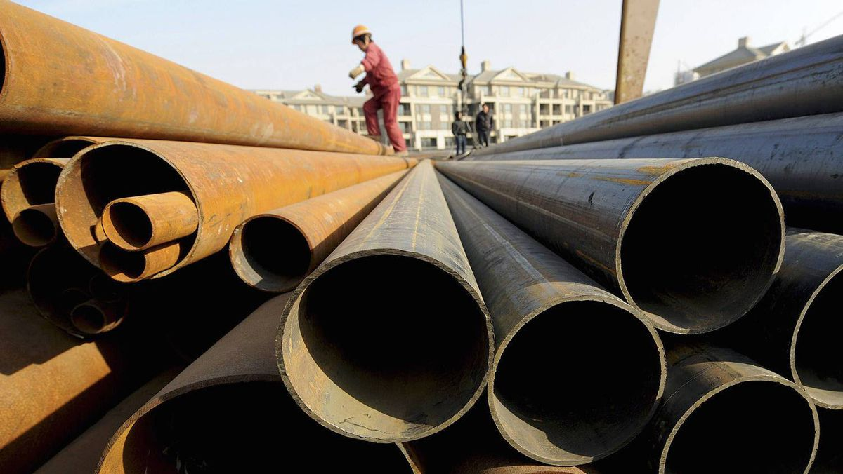 A labourer walks on steel pipes at a steel market in Hefei, Anhui province