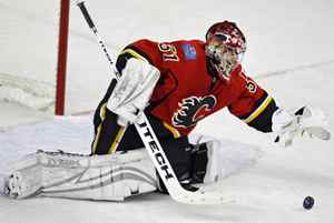 Calgary Flames goalie Curtis Joseph reaches for the puck during second period NHL Western Conference quarter-final hockey action in Calgary, Sunday, April 13, 2008. The Flames beat the Sharks 4-3 to take the lead in the best of seven series 2-1.THE CANADIAN PRESS/Jeff McIntosh