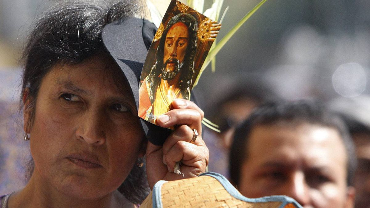 A woman holds an image of Jesus during a Holy Week procession honoring the Lord of Miracles, Lima's patron saint, on Good Friday in Lima, Peru, Friday April 6, 2012.