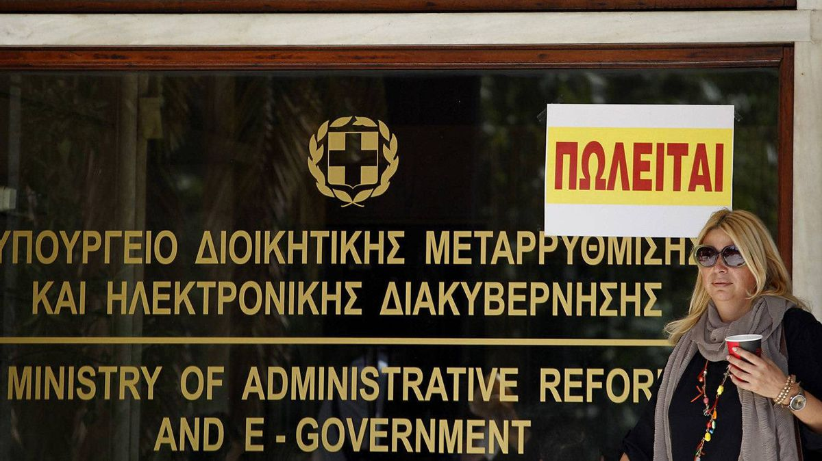 "A civil servant walks in front of the entrance of an Interior Ministry building with a sign reading, ""For Sale,"" top right, in central Athens, on Sept. 29, 2011. Protesting civil servants occupied several ministry buildings, including the Finance Ministry, ahead of a visit later Thursday by international debt inspectors to decide on whether to release the next vital installment for rescue loans to debt-shackled Greece."