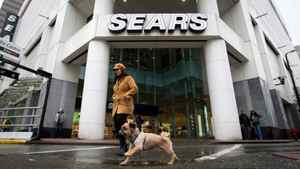 A woman walks her dog past the Sears store in downtown Vancouver, B.C., on Friday March 2, 2012.