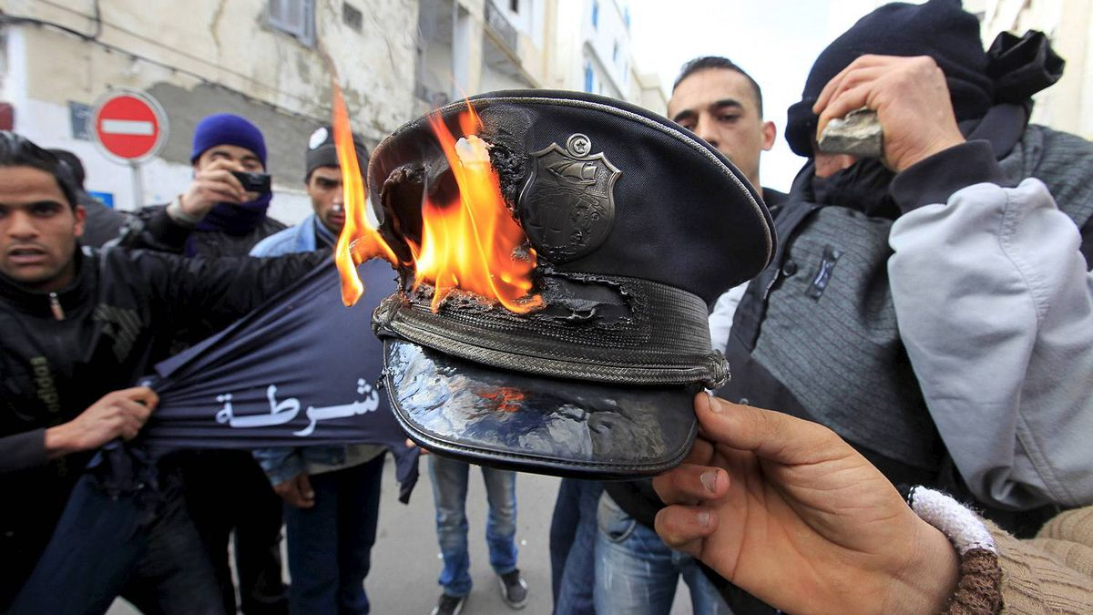 Rioters burn a police officer's hat during clashes with the police in the capital Tunis Jan. 14, 2011.