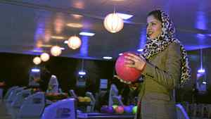 Meena Rahmani, 26, owner of The Strikers, the country's first bowling center, holds a bowling ball in Kabul, Afghanistan. In an Afghan capital scarred by years of war, a young Afghan woman has bet $1 million that the country could use a chance to have a bit of fun _ by bowling. Located just down the street from Kabul's glitziest mall, Meena Rahmani opened Afghanistan's first bowling alley, offering a place where Afghan men, women and families can gather, relax, bowl a few games and not be burdened by the social, religious and cultural restrictions that govern daily life in the impoverished country.