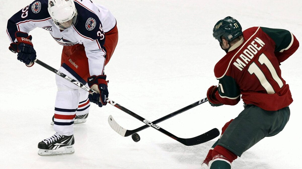 Minnesota Wild's John Madden, right, battles Columbus Blue Jackets' Jan Hejda, left, for possession in overtime of an NHL hockey game, Saturday, March 19, 2011, in St. Paul, Minn. Columbus defeated Minnesota 5-4 in overtime. (AP Photo/Genevieve Ross)