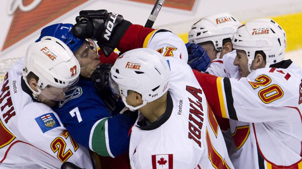 Calgary Flames defenseman Derek Smith (27), left to right, Jarome Iginla (12) and Curtis Glencross (20) gang up on Vancouver Canucks left wing David Booth (7) after Booth had goaltender interference during third period NHL hockey action at Rogers Arena in Vancouver, B.C. Sunday, Dec, 4, 2011. The Canucks won 5-1. THE CANADIAN PRESS/Jonathan Hayward
