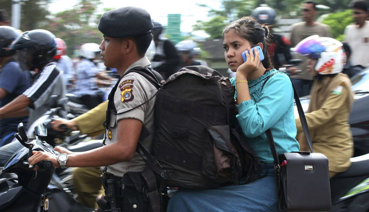 A policeman evacuates his wife in a motorcycle in Banda Aceh after a strong earthquake struck Indonesia province April 11, 2012.