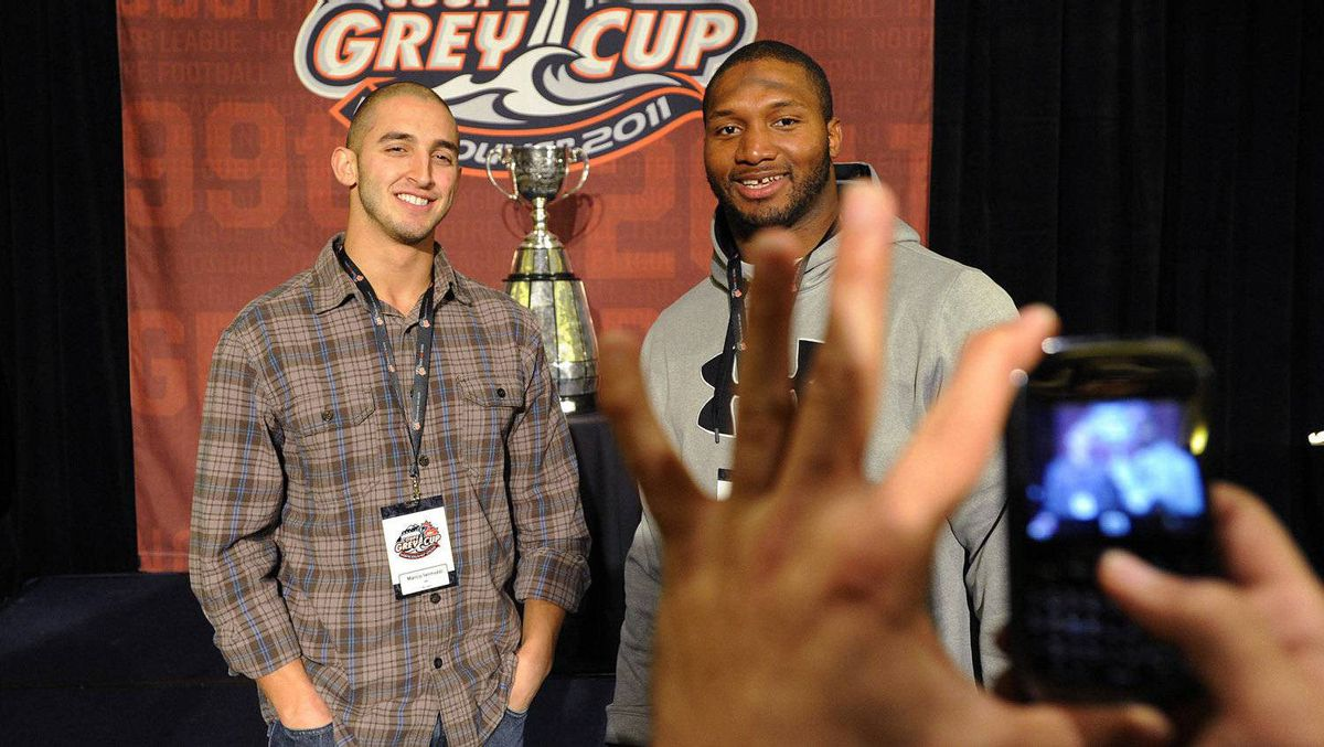 BC Lions' Marco Iannuzzi (L) and Rolly Lumbala get their photo taken with the CFL's Grey Cup during their team lunch in Vancouver, British Columbia November 24, 2011. The BC Lions will play the Winnipeg Blue Bombers in the CFL's 99th Grey Cup football game this Sunday, November 27, 2011. REUTERS/Todd Korol
