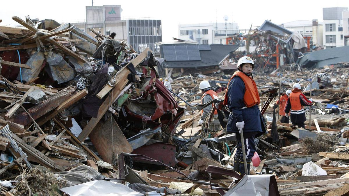 Volunteer firefighters search for victims of Friday's tsunami at Rikuzentakada, Iwate Prefecture, northern Japan, Sunday, March 13, 2011.