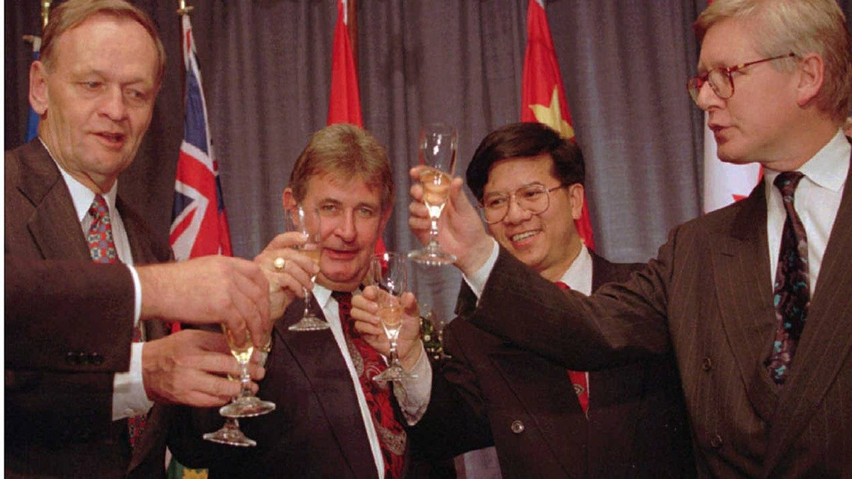 Prime Minister Jean Chretien is joined by (left to right) Mr. Klein, the Canadian minister for Asia Pacific relations, and Ontario Premier Bob Rae for a toast following the signing ceremony of 54 Canadian companies with Chinese interests in 1994.