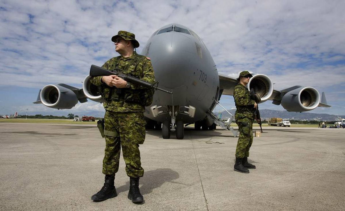 Two military police officers from CFB Trenton, Ontario stand watch at the front of a Canadian C-17 Globemaster aircraft that had just landed, shortly after 1:30pm local time today, carrying troops, equipment, into the earthquake ravaged country. At left is MCpl Mike Lehman, and at right is Cpl Curtys Kennedy.