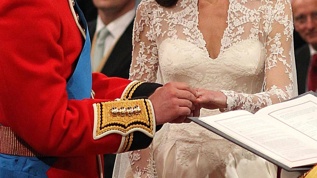 Prince William places a ring on Kate Middleton in front of the Archbishop of Canterbury at Westminster Abbey, on April 29, 2011 in London