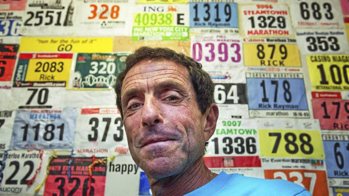 Rick Rayman stands in front of a wall of his running bibs and jackets he's recevied from some of the 231 marathons he's run since he began running in 1978.