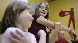 Cassidy Robinson, right, and her little buddy Lauren Hardt stretch after completing the Healthy Buddies fitness loop in the gym of their school in Sechelt, B.C.