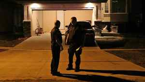 Police stand in front of a garage in Winnipeg, Sunday Aug. 14, 2011.