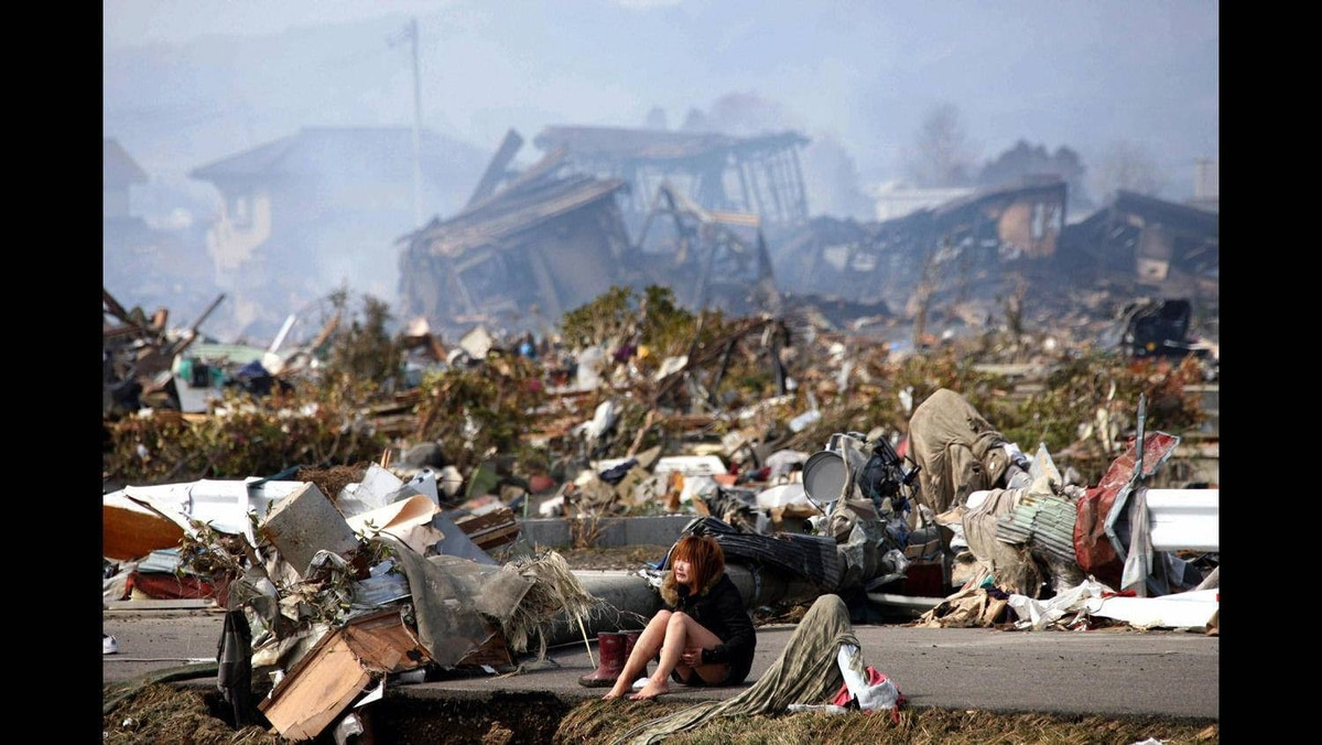 A woman cries while sitting on a road amid the destroyed city of Natori, Miyagi Prefecture in northern Japan March 13, 2011, following a massive earthquake and tsunami.
