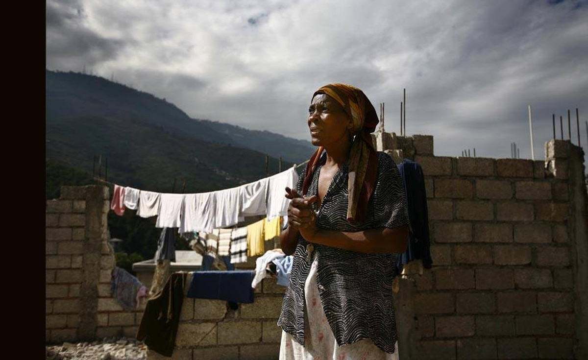 Serbio Francieon stands up in front of her destroyed home in Petronville, a damaged middle-class neighborhood.