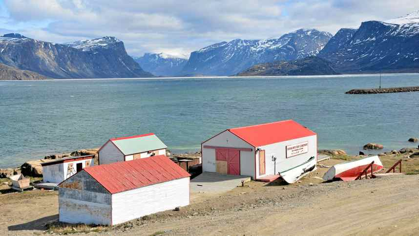 The shoreline of Pangnirtung with the HBC post buildings. Pangnirtung Pass is in the background.