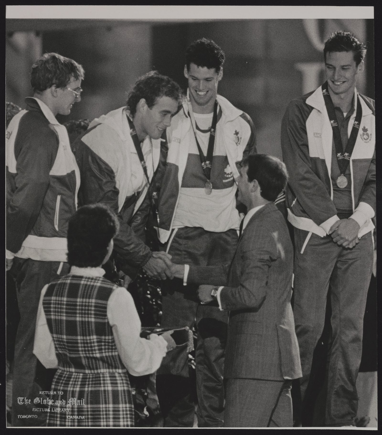 The notes transcribed from the back of this photograph are as follows: COMMONWEALTH GAMES EDINBURGH (1986) SPECIAL FOR THE GLOBE AND MAIL, CANADA EDI11: EDINBURGH, SCOTLAND, JULY 30-Prince Edward presents Victor Davis with a gold medal as the rest of the Canadian 4x100m Medley team look on. From (L-R) Tom Ponting Victor Davis, Mark Tewksbury and Alex Baumann. REUTER hd/Hans Deryk