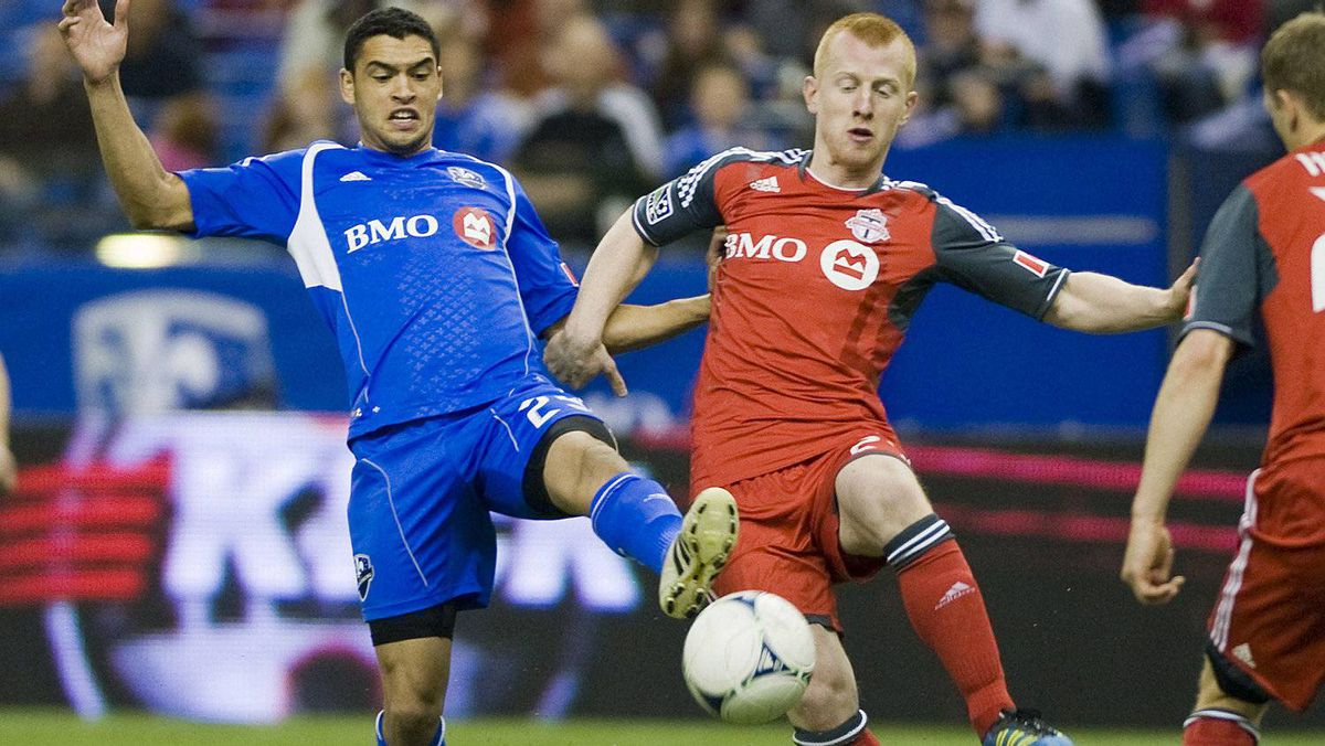 Montreal Impact's Lamar Neagle, left, and Toronto FC's Richard Eckersley battle for the ball during second half in Montreal, Saturday, April 7, 2012.