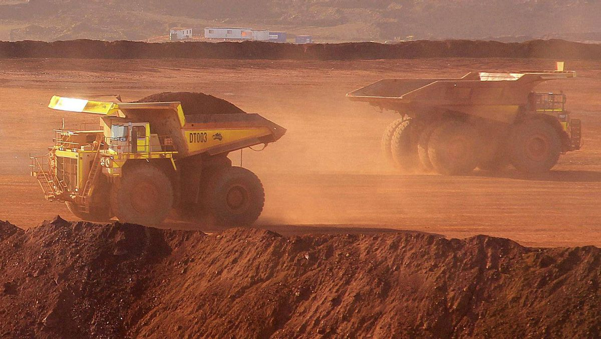 Heavy equipment operate at an iron ore mine.