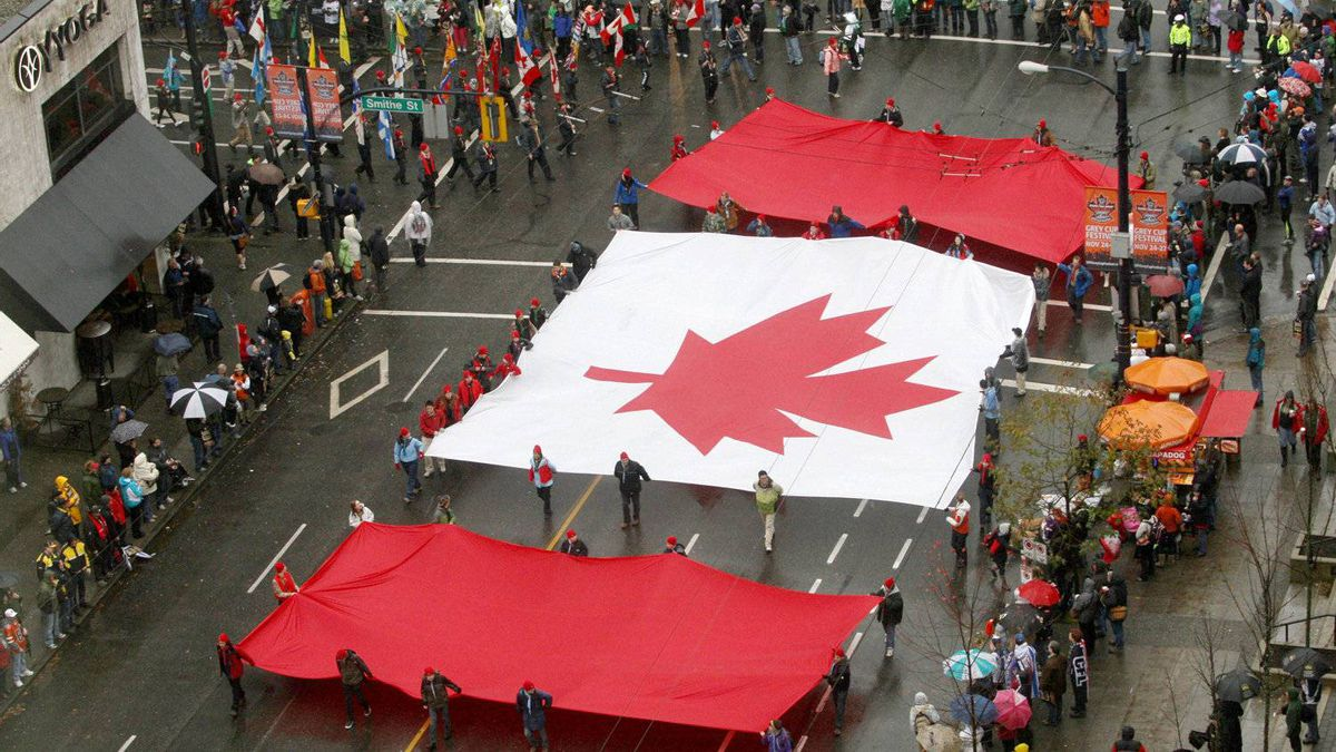 A large Canadian flag is carried down the street of downtown Vancouver Saturday November 26, 2011 during the Grey Cup parade. The B.C. Lions will face the Winnipeg Blue Bombers in the 99th Grey Cup CFL football final Sunday. THE CANADIAN PRESS/Ryan Remiorz