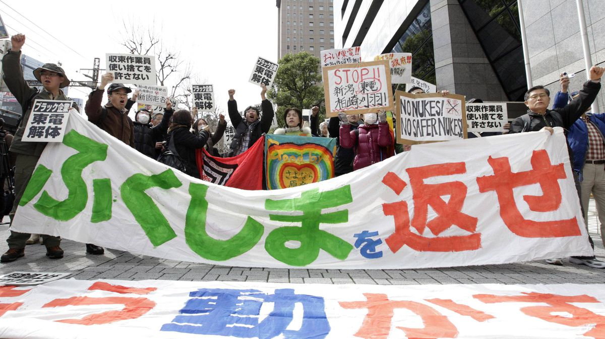 Anti-nuclear protesters hold a banner reading 'give us back Fukushima' in front of the headquarters of Tokyo Electric Power Co. in Tokyo on Sunday.