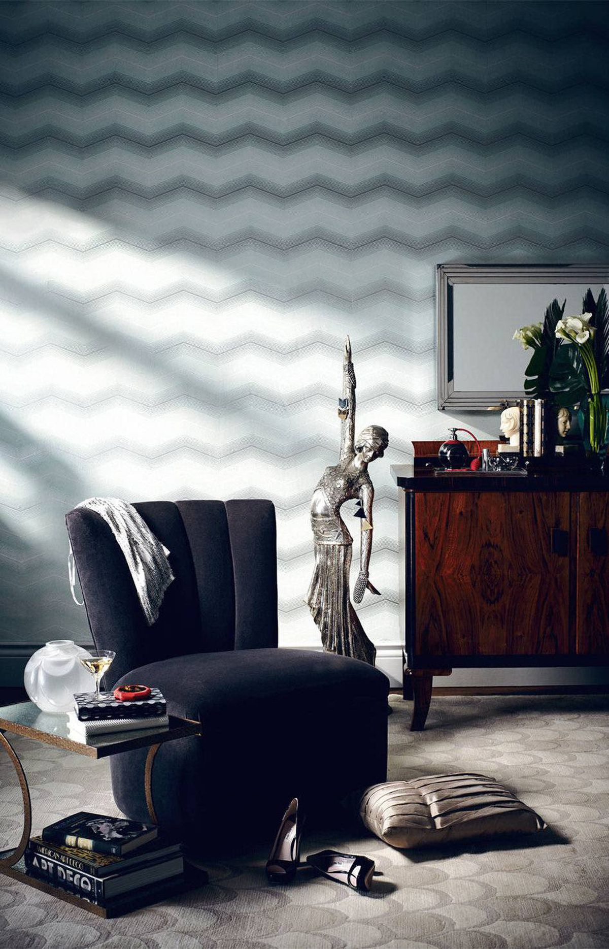 SOFTEN THE EDGES It's the signature mix of strong lines and soft curves that sets art deco apart from other styles. The graphic chevron wallpaper hanging here complements the shapely forms of a shell-patterned carpet and velvet slipper chair.