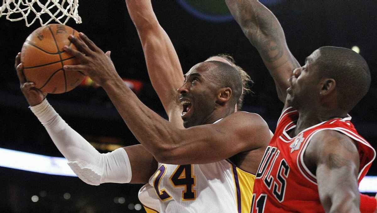 Los Angeles Lakers Kobe Bryant goes to the basket to score past Chicago Bulls Ronnie Brewer (R) and Joakim Noah (back) during the first quarter of their NBA basketball game in Los Angeles December 25, 2011. REUTERS/Danny Moloshok