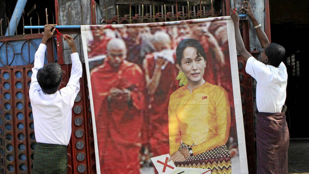 Members of the National Democratic Force party (NDF) put up a poster of Myanmar's detained opposition leader Aung San Suu Kyi at the gate to the party's headquarters in Yangon, Myanmar, Friday, Nov. 5, 2010. Political gatherings are only allowed with a week's notice and an official review of the campaign speech. Hundreds of potential opposition candidates, including pro-democracy hero Aung San Suu Kyi, are under house arrest or in prison. Many of the rules were clearly written to benefit the proxy party for the ruling junta.
