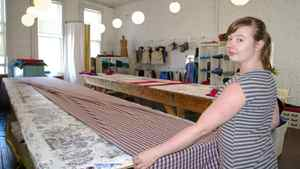 Employee Renee Crawford lays out a bolt of fabric in the Smoking Lily studio.