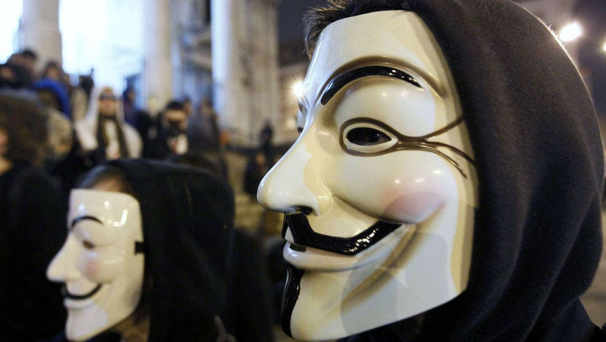 "A protester wearing a Guy Fawkes mask, symbolic of the hacktivist group ""Anonymous"", takes part in a protest in central Brussels January 28, 2012."