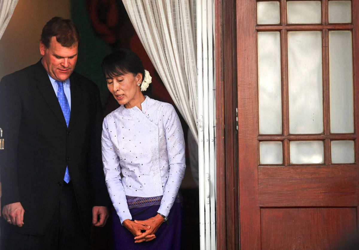 Myanmar's pro-democracy leader Aung San Suu Kyi and Canada's Foreign Minister John Baird exit Suu Kyi's home after their meeting in Yangon.