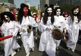 South Korean prostitutes in mourning clothes and with painted faces, march during a rally in Seoul, South Korea. Hundreds of prostitutes and pimps rallied Tuesday near a red-light district in Seoul to protest a police crackdown on brothels.