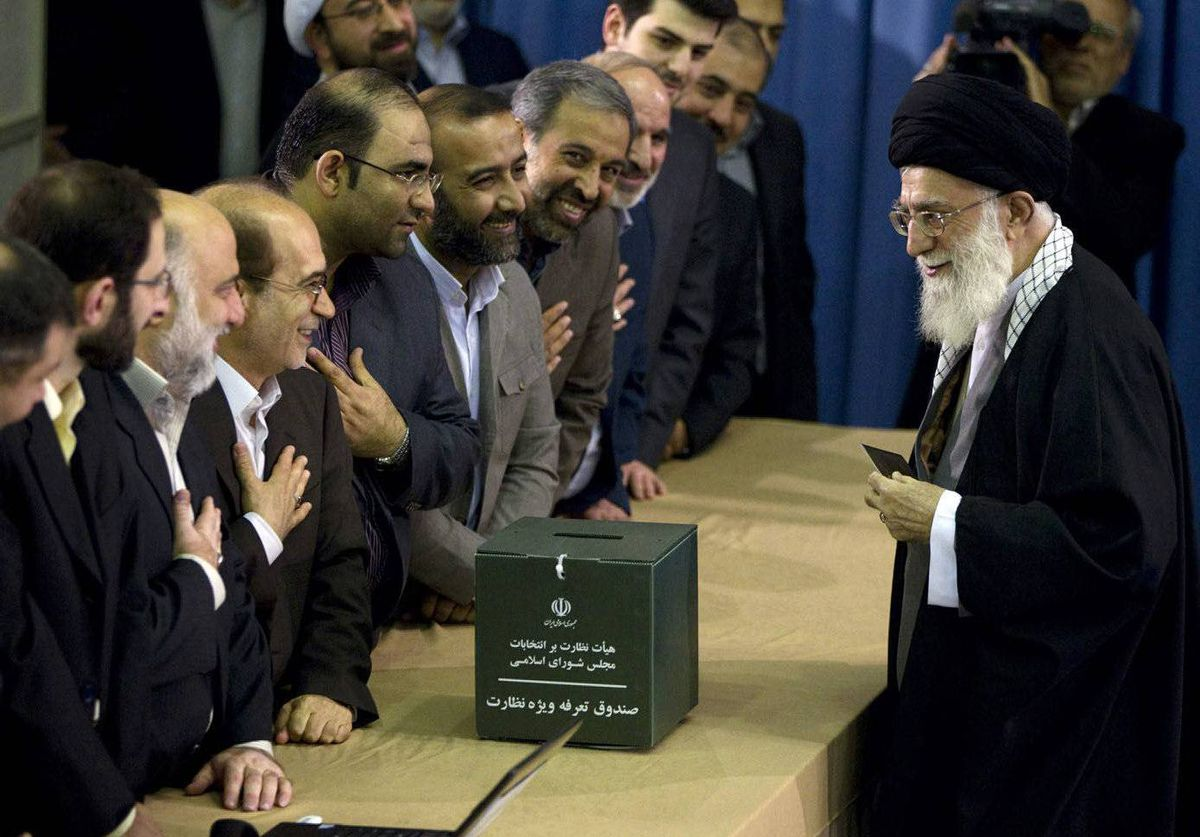 Iran's Supreme Leader Ayatollah Ali Khamenei greets election officials as he presents his identification papers to cast his ballot in the parliamentary election in Tehran.