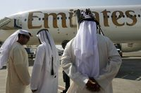 Passengers wait to board an Emirates airplane at Dubai airport in this Sept. 7, 2007 file photo.