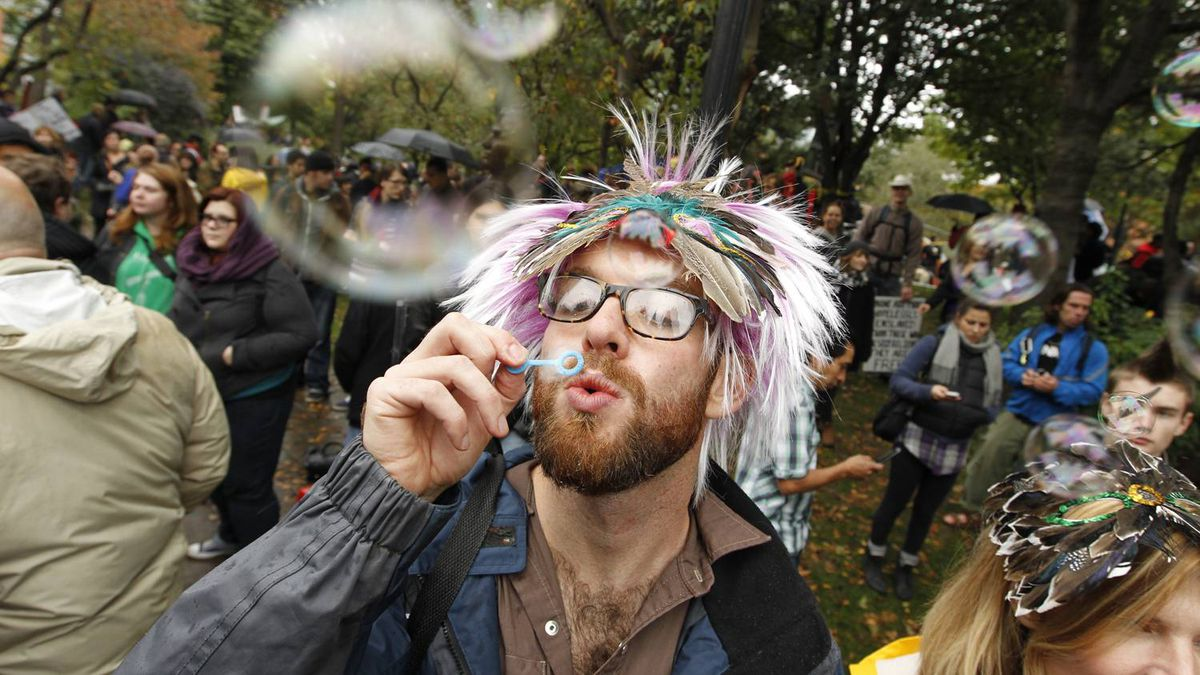 A man blows bubbles as Occupy Toronto protesters gather in St. James Park on October 15, 2011.