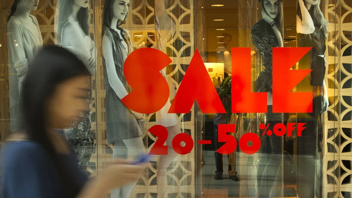 A shopper passes a sale sign at the Eaton Centre in Toronto in this file photo.
