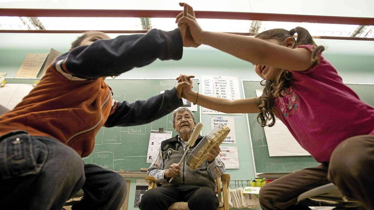 Lukis Jules, 4 years old,left, plays a traditional game with Suli Sotit ,5 years odl as Native Elder Lawrence Michel plays the drum and sings to the pre-school kids at Chief Atahm School in Chase, B.C. on Wednesday November 17, 2010. The Elders are invited to teach the traditional ways to the young students. Aboriginal leaders in B.C. are on the brink of re-inventing education for children on reserves. Now they're fighting for funding.