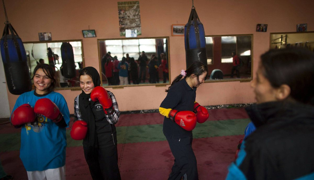 Afghan women share a light moment during a practice session inside a boxing club in Kabul December 28, 2011.