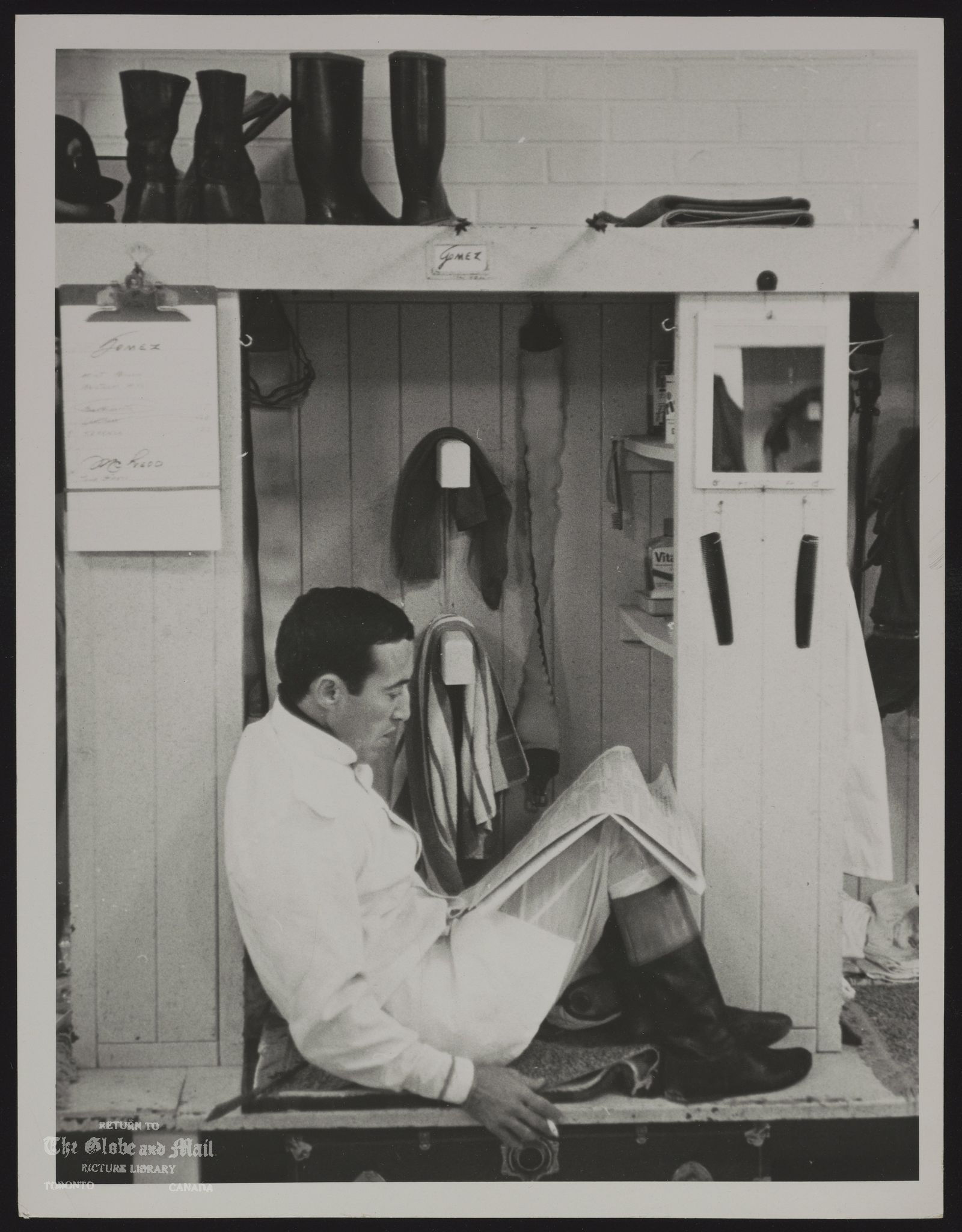 Avelino GOMEZ Jockey A smoke and a glance at a newspaper while awaiting call. Photo used oct. 8/66